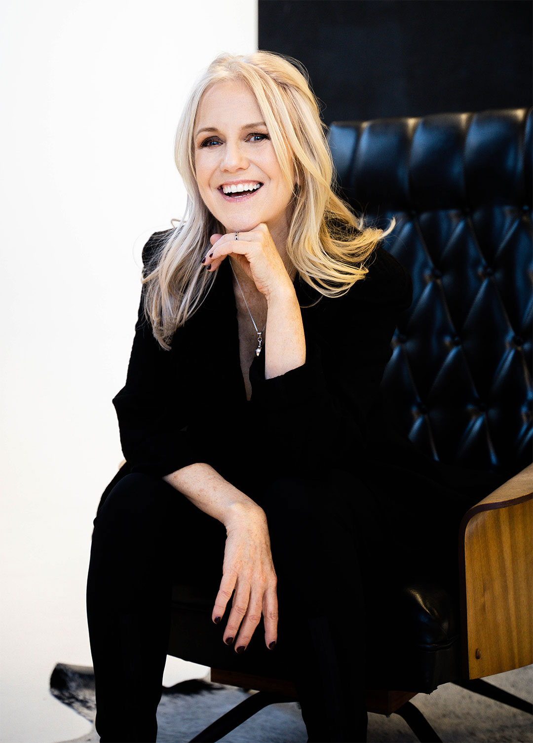 Nina Rolle smiling and wearing a black suit while sitting in a black leather armchair